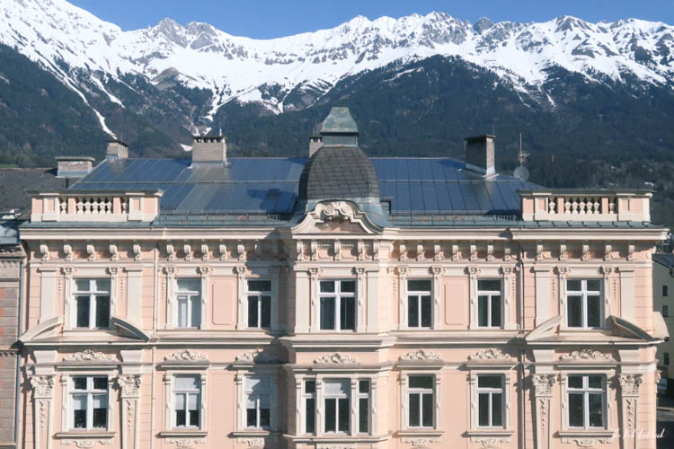 Innsbruck Ultimate Travel Guide Pink Buidling and Mountains
